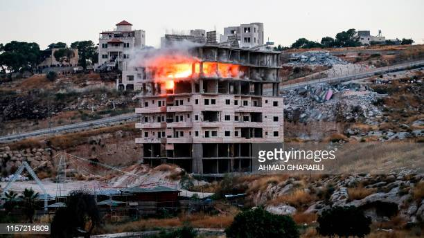 This picture taken on July 22 shows the demolition of a Palestinian building which was under construction in the Palestinian village of Sur Baher in...