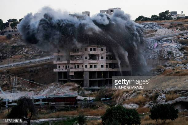 This picture taken on July 22 shows the demolition of a Palestinian building which was under construction, in the Palestinian village of Sur Baher in...