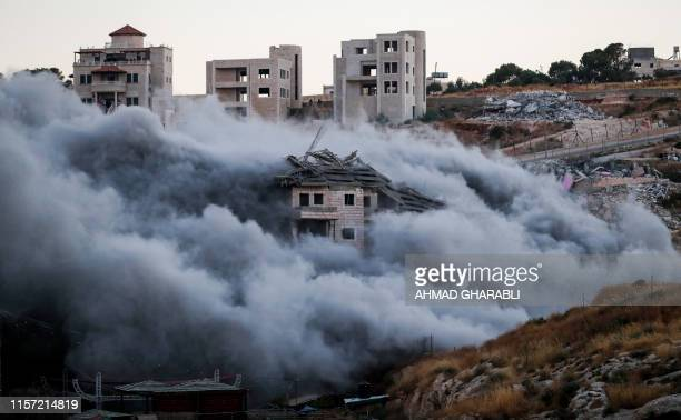 This picture taken on July 22 shows the demolition of a Palestinian building which was under construction, in the the Palestinian village of Sur...