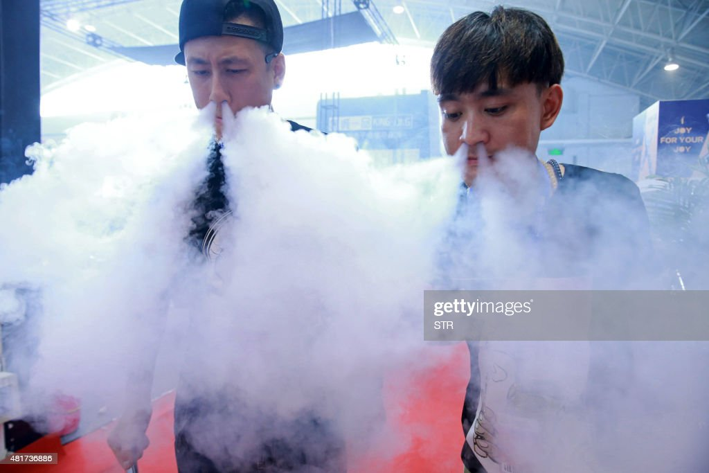 This picture taken on July 23, 2015 shows sales staff exhaling vapour while demonstrating their electronic cigarette products at the Beijing International Vapor Distribution Alliance Expo, or the Vape China Expo, at the China International Exhibition Center in Beijing. CHINA