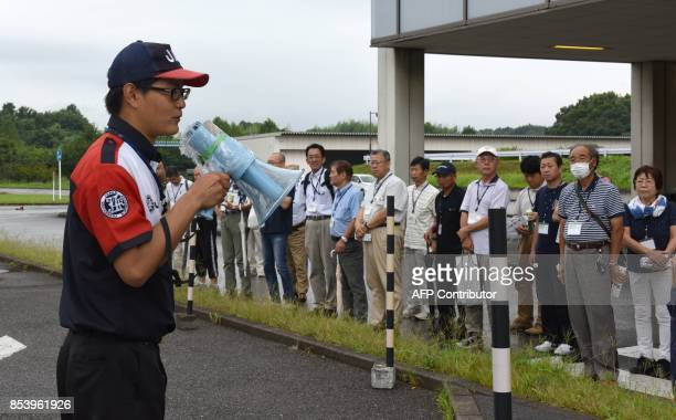This picture taken on July 23 2017 shows an instructor addressing participants of a driving school for senior citizens managed by the Japan...
