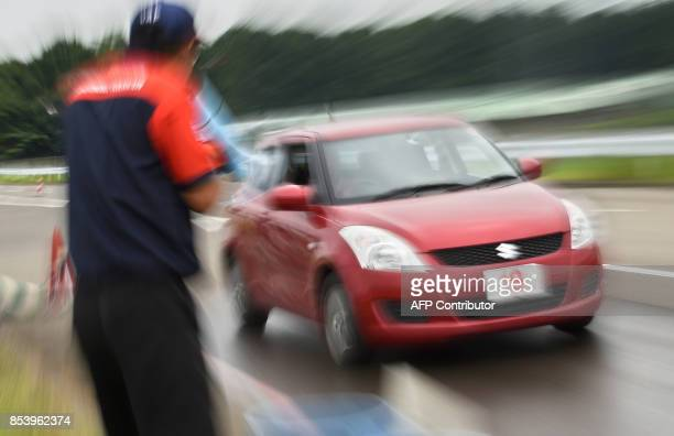 This picture taken on July 23 2017 shows an instructor keeping watch during an emergency brake run at a driving school for senior citizens managed by...