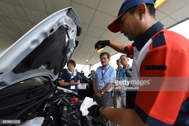 This picture taken on July 23 2017 shows an instructor using a dipstick to check engine oil levels during a lesson on car maintenance at a driving...