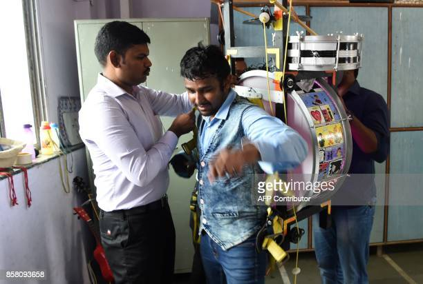 This picture taken on July 23 2017 shows Indian singer and songwriter Gladson Peter removing his musical rig after a performance in Mumbai The...