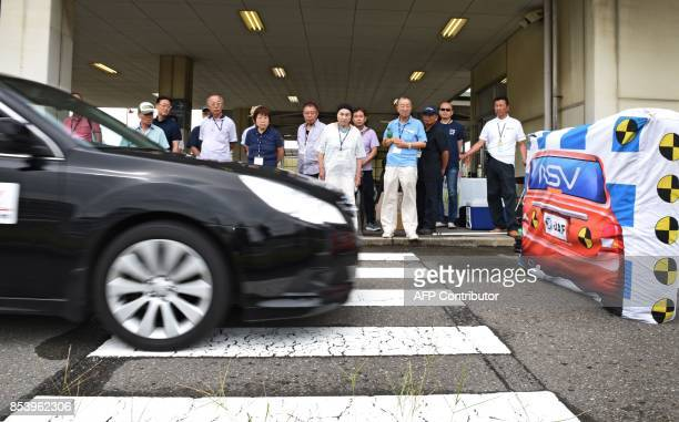 This picture taken on July 23 2017 shows participants watching a demonstration of a car's automatic stop system at a driving school for senior...