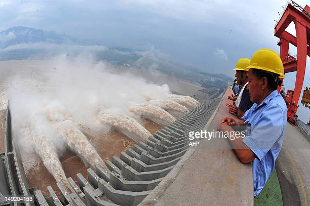 This picture taken on July 24, 2012 shows workers watching as water is released from the Three Gorges Dam, a gigantic hydropower project on the...