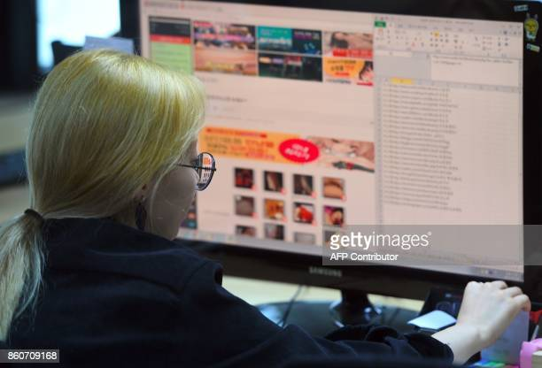 This picture taken on July 24 2017 shows an employee of Santa Cruise 'digital laundry' company monitoring a computer screen to find 'revenge porn' at...