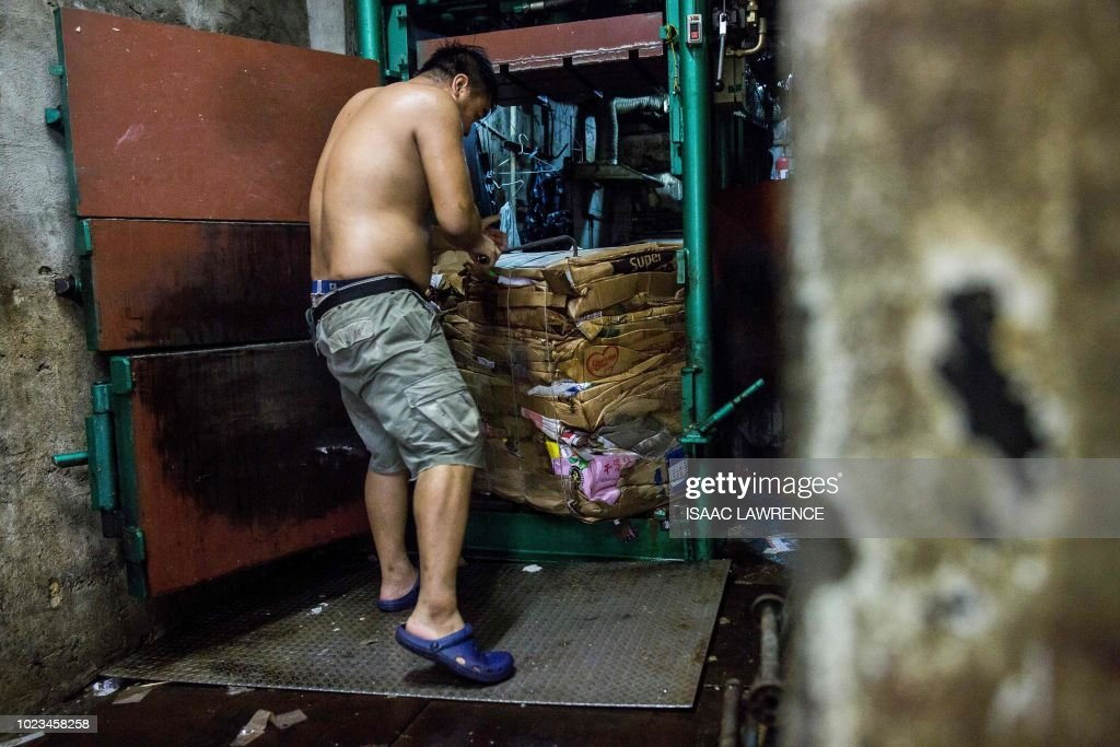 This picture taken on July 24, 2018 shows a worker lifting compressed cardboard out of an industrial compactor at a recycling depot in the Wan Chai district of Hong Kong - Cardboard collectors pick up discarded packing boxes from shops, markets and residential buildings, selling them for a few dollars to recycling depots, where cardboard is more valuable than plastic. The depots then ship it abroad -- up to 95 percent of it to mainland China in 2016, according to local authorities -- as Hong Kong has no recycling plants of its own to convert it into usable materials. (Photo by ISAAC LAWRENCE / AFP) / TO GO WITH HongKong-social-environment-elderly-cardboard-collector, FEATURE by Yan ZHAO