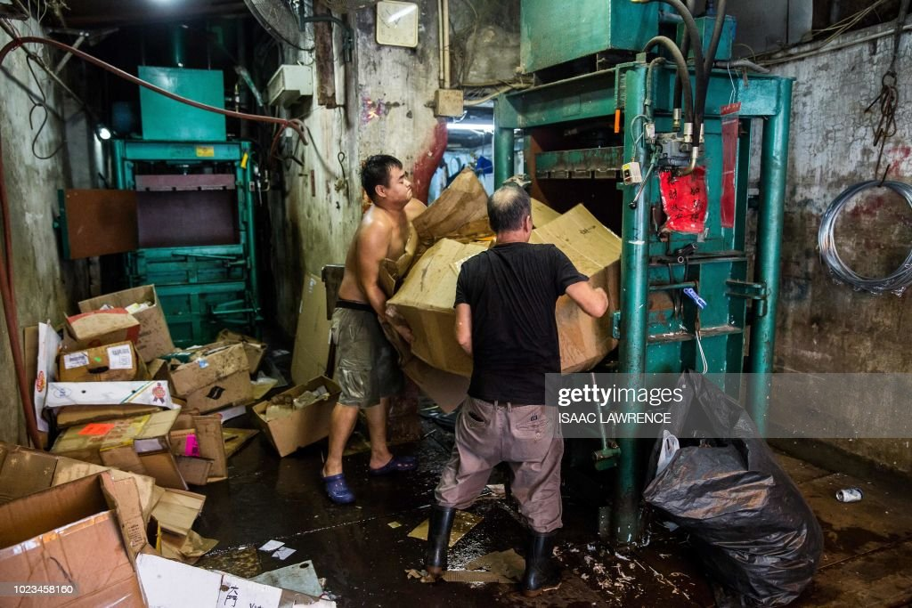 This picture taken on July 24, 2018 shows workers at a recycling depot loading cardboard into an industrial compactor in the Wan Chai district of Hong Kong. - Cardboard collectors pick up discarded packing boxes from shops, markets and residential buildings, selling them for a few dollars to recycling depots, where cardboard is more valuable than plastic. The depots then ship it abroad -- up to 95 percent of it to mainland China in 2016, according to local authorities -- as Hong Kong has no recycling plants of its own to convert it into usable materials. (Photo by ISAAC LAWRENCE / AFP) / TO GO WITH HongKong-social-environment-elderly-cardboard-collector, FEATURE by Yan ZHAO