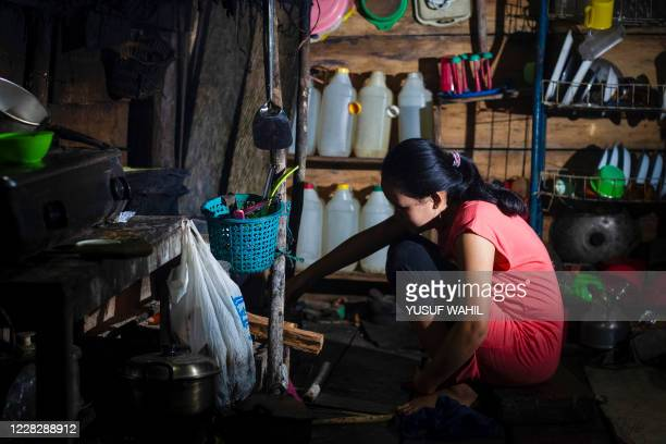 This picture taken on July 24, 2020 shows Tati , who got married under age in March 2020, cooking in her kitchen in North Botteng in Mamuju, West...