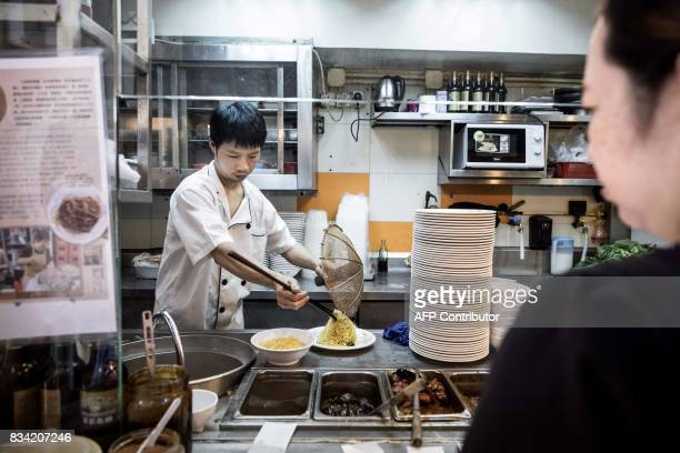 This picture taken on July 25 2017 shows a waitress watching as a chef serves noodles handmade using a traditional bamboo pole technique at a...