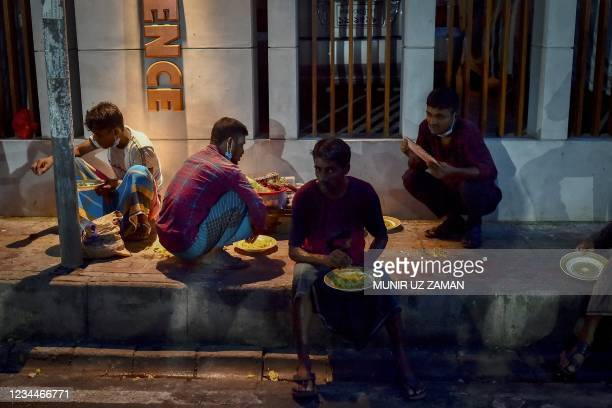 This picture taken on July 26, 2021 shows pandemic affected people eating food distributed by Mehmankhana, a non-profit organization, working for...
