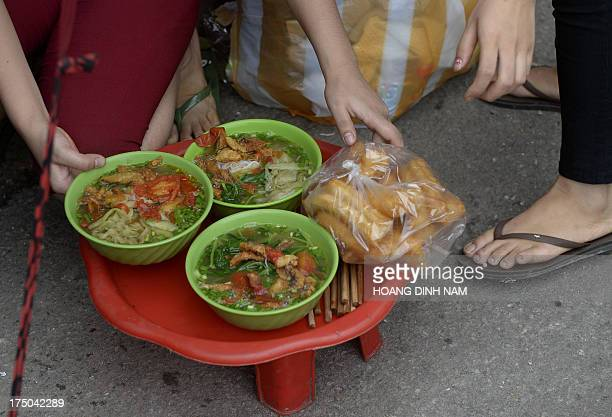 This picture taken on July 26 shows a vendor preparing to deliver bowls of noodle to customers at a streetside food stall in downtown Hanoi Some 75...