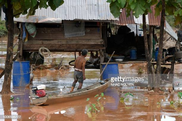 This picture taken on July 27, 2018 shows a resident returning to his homes from Sanamxai district, Attapeu province, after floodwaters from a dam...
