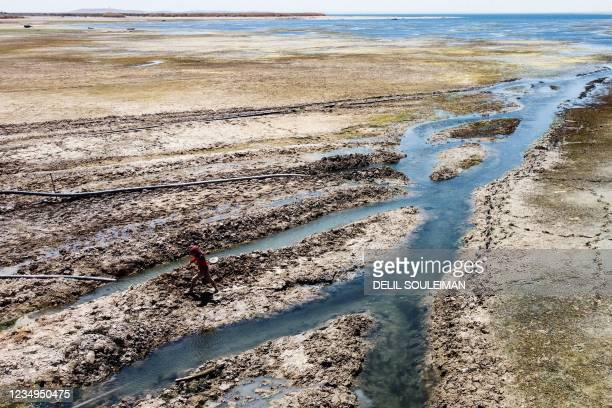 This picture taken on July 27, 2021 shows an aerial view of a man walking past a water pump drawing water from the Lake Assad reservoir, in the...