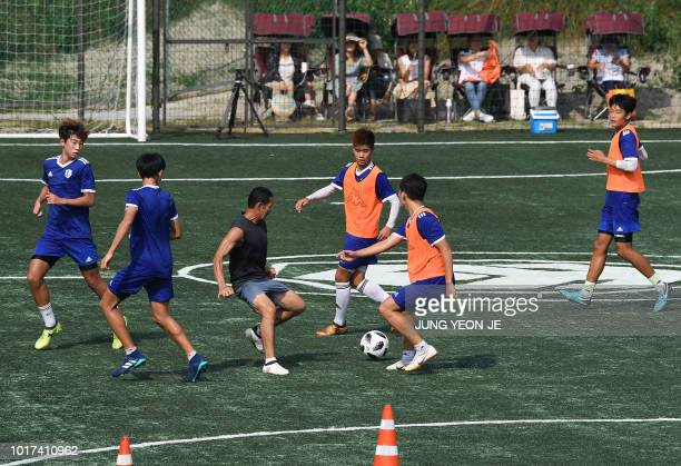 This picture taken on July 28 2018 shows South Korean teenagers on the pitch with Son Woongjung father of South Korean football star Son Heungmin as...