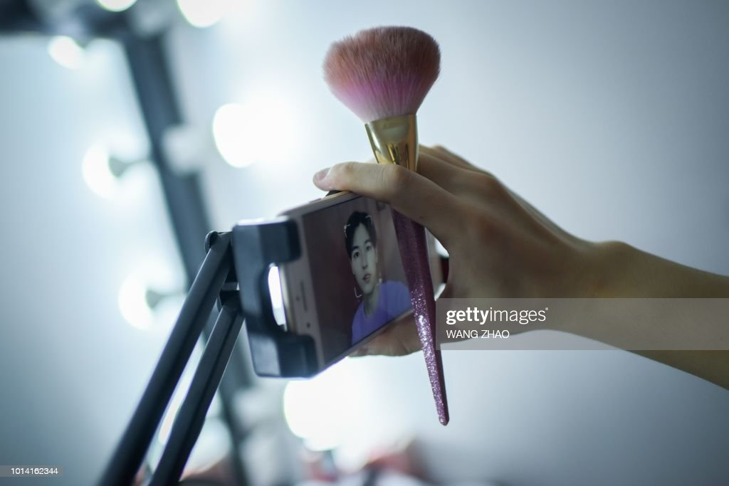 This picture taken on July 29, 2018 shows Jiang Cheng preparing for a live at his home in Beijing. - When Jiang Cheng first tried a bit of concealer during his first year of university in China it gave him self-confidence and he was instantly hooked. Now he is among hundreds of Chinese men sharing beauty tips online and cashing in on the booming male cosmetics industry. (Photo by WANG ZHAO / AFP)