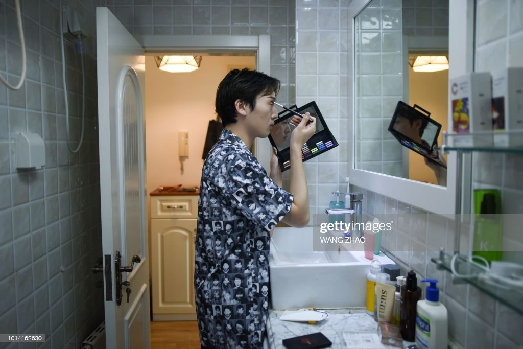 This picture taken on July 29, 2018 shows Lan Haoyi doing make up before recording video at his home in Beijing. - When Jiang Cheng first tried a bit of concealer during his first year of university in China it gave him self-confidence and he was instantly hooked. Now he is among hundreds of Chinese men sharing beauty tips online and cashing in on the booming male cosmetics industry. (Photo by WANG ZHAO / AFP)