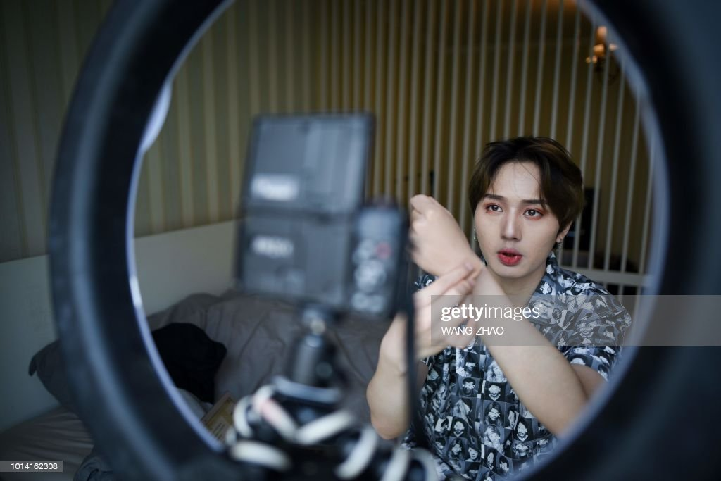 This picture taken on July 29, 2018 shows Lan Haoyi introducing a cosmetic product during recording video at his home in Beijing. - When Jiang Cheng first tried a bit of concealer during his first year of university in China it gave him self-confidence and he was instantly hooked. Now he is among hundreds of Chinese men sharing beauty tips online and cashing in on the booming male cosmetics industry. (Photo by WANG ZHAO / AFP)