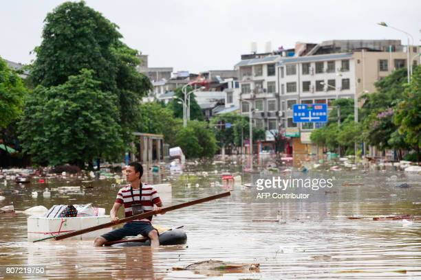 This picture taken on July 3 2017 shows a man using an improvised flotation device to move through floodwaters on a flooded street in Liuzhou Guangxi...