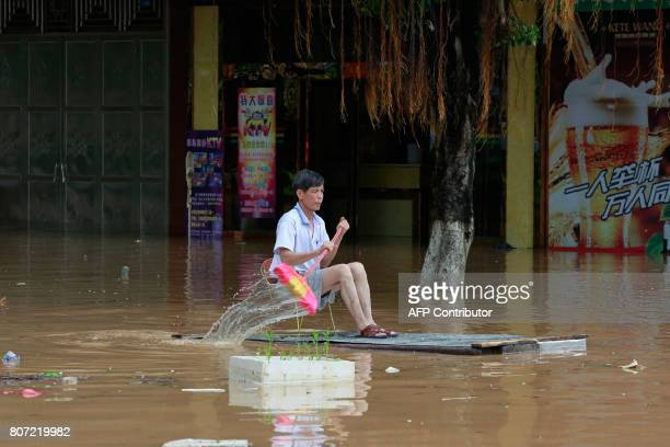 TOPSHOT This picture taken on July 3 2017 shows a man using an improvised flotation device to move through floodwaters on a flooded street in Liuzhou...