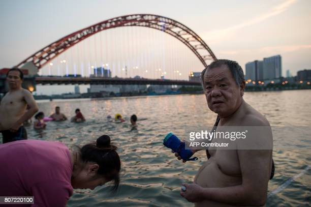 This picture taken on July 3 2017 shows people standing in the Yangtze River along the River Beach Park in Wuhan Hubei Province after heavy rains...