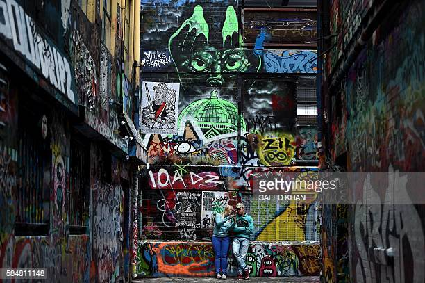 This picture taken on July 30 2016 shows visitors amid street art in the famous graffiti lanes of Melbourne Hosier Lane and Rutledge Lane are two of...