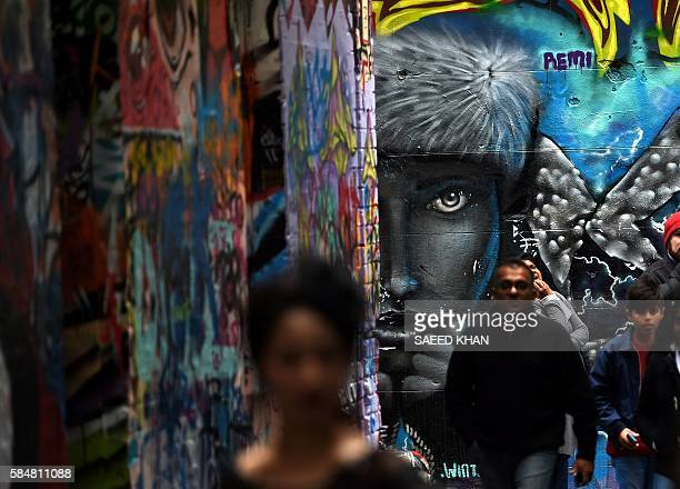 This picture taken on July 30 2016 shows visitors looking at street art in the famous graffiti lanes of Melbourne Hosier Lane and Rutledge Lane are...