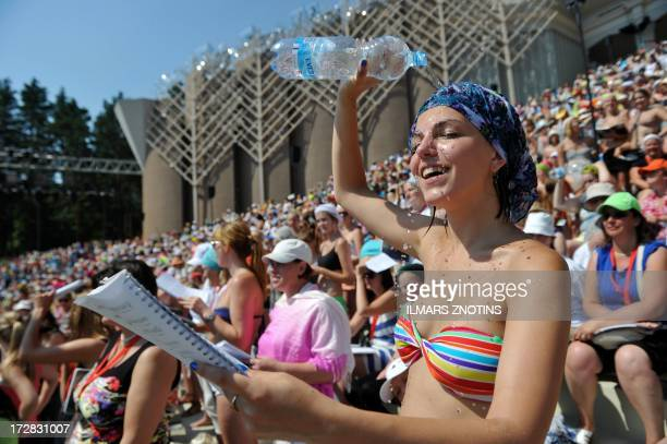 COLLIER This picture taken on July 4 2013 shows a woman pouring water over her head during a rehearshal at the Song and Dance festival in Riga Latvia...
