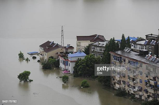 This picture taken on July 5, 2016 shows trees and houses submerged by floodwaters in Zongyang county, in east China's Anhui province. Heavy rain...