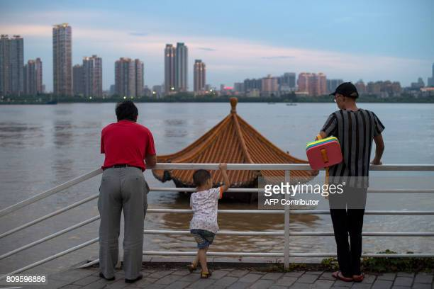 This picture taken on July 5 2017 shows people standing on a dock in the Yangtze River along the River Beach Park in Wuhan Hubei Province after heavy...