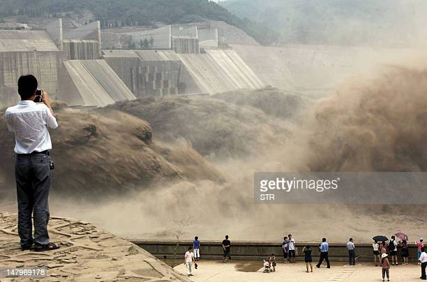 This picture taken on July 6 2012 shows visitors gathering to watch giant gushes of water being released from the Xiaolangdi dam to clear up the...