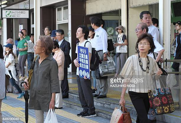 This picture taken on July 6, 2016 shows pedestrians listening to an election campaign speech by a candidate of the main opposition party in Tokyo....