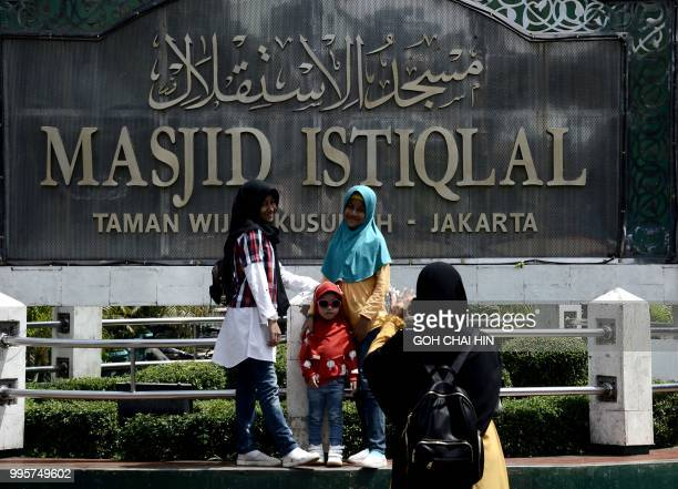 This picture taken on July 6 2018 shows a group of Indonesian Muslim women gathering to take photos at the Istiqlal mosque in Jakarta A small number...
