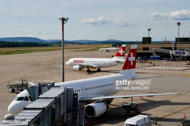 This picture taken on July 6 shows an Airbus A320 parked and an Airbus A319 of the Swiss International Airlines taxiing on the tarmac at the Zurich...
