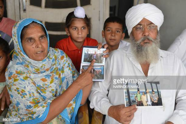 This picture taken on July 6 shows Narinder Kaur 54 along with her husband Gurmej Singh 60 showing photographs of her son Deepak Singh as she is...