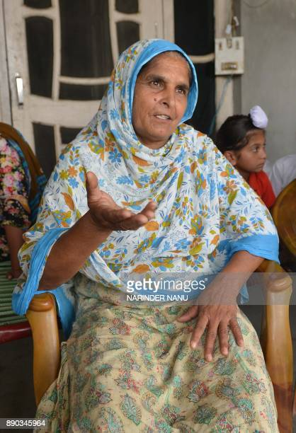 This picture taken on July 6 shows Narinder Kaur 54 showing photographs of her son Deepak Singh as she is talking with media at their residence in...