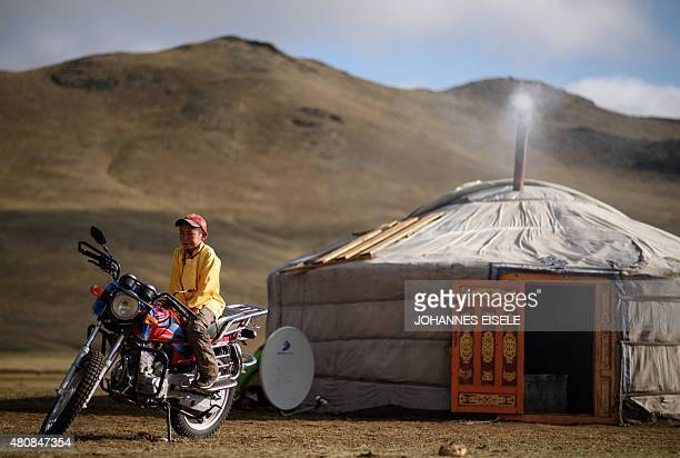 This picture taken on July 8 2015 shows 13yearold jockey Purevsurengiin Togtokhsuren sitting on a motorbike next to his 'yurt' after taking care of...
