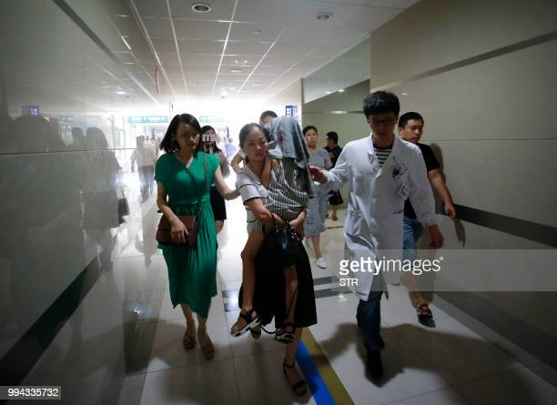 This picture taken on July 8 2018 shows a girl a survivor of a capsized Thailand tourist boat arriving to receive medical treatment at a hospital in...