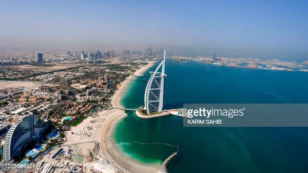 This picture taken on July 8, 2020 shows an aerial view of the Burj al-Arab hotel in the Gulf emirate of Dubai, with the man-made Palm Jumeirah...