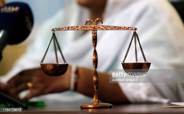 This picture taken on July 9, 2019 shows a miniature scale appearing during a press conference by Sudanese lawyer Abdelazim al-Hassan who filed a...