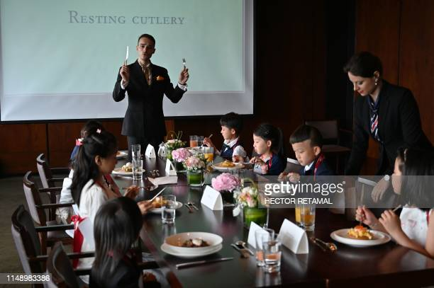 This picture taken on June 1 2019 shows Guillaume de Bernadac teaching children how to use cutlery during an etiquette and manners class in central...
