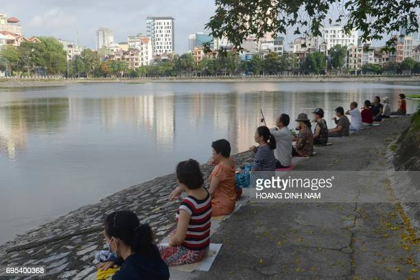 This picture taken on June 10 2017 shows residents practicing Falun Gong meditation exercises next to a lake in downtown Hanoi / AFP PHOTO / HOANG...
