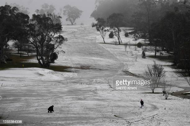 This picture taken on June 10, 2021 shows a family enjoying the first snowfall of the season at a golf course in the Blue Mountains.