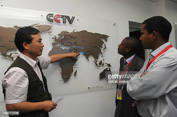 This picture taken on June 12 2012 shows the managing editor of China Central Television Africa Pang Xinhua talking to local journalist as he shows...
