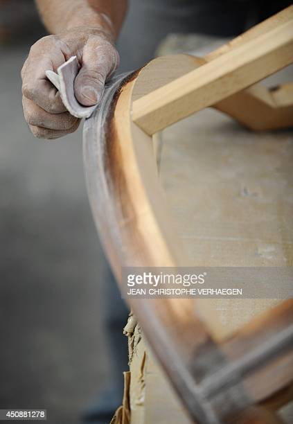 This picture taken on June 12 2014 shows a worker sanding a chair in the workshop of French luxury furniture maker CounotBlandin in LiffolleGrand...