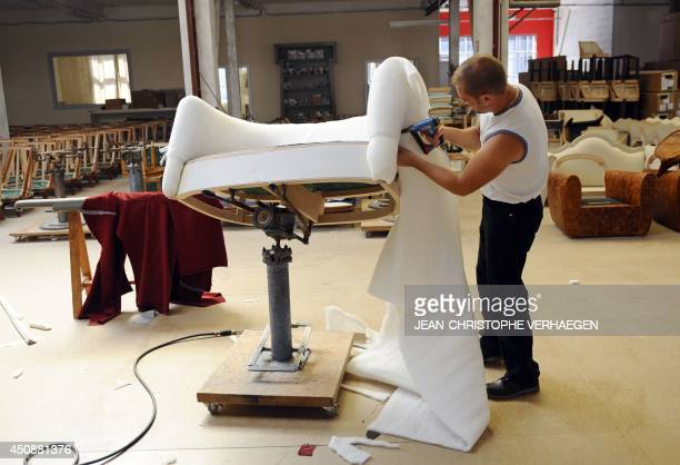 This picture taken on June 12 2014 shows a worker working on a chair in the workshop of French luxury furniture maker CounotBlandin in LiffolleGrand...