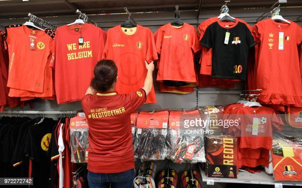 This picture taken on June 12 2018 shows an employee adjusting shirts with the logo of the Belgium national football team 'the Red Devils' on sale at...