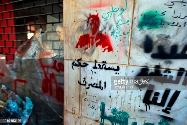 This picture taken on June 12, 2020 shows a view of a graffiti depicting the Governor of the Banque du Liban Riad Salame with horns, with text below...