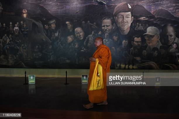 """This picture taken on June 13, 2019 shows a Buddhist monk walking past a mural illustrating the rescue of the 12 boys from the """"Wild Boars"""" football..."""